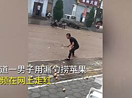 暴雨中男子用漏勺在门口捞苹果