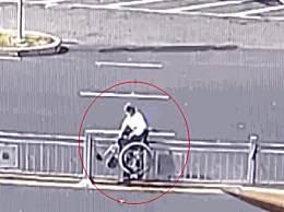 大爷坐轮椅横穿马路翻护栏